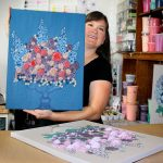 Artist Bethany Ogle holding the first painting in the new floral still life series for 2017