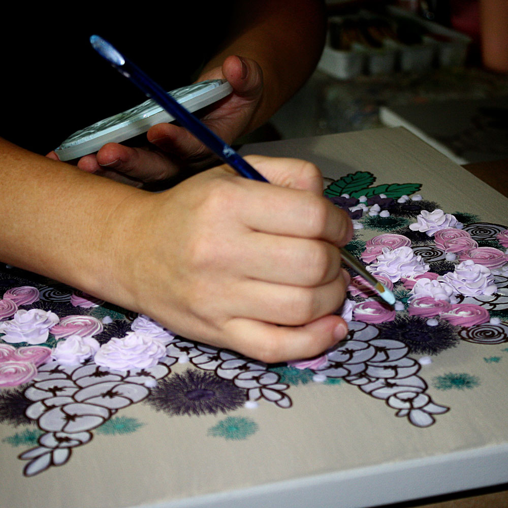 Close up of artist sculpting 3d flowers onto a canvas painting