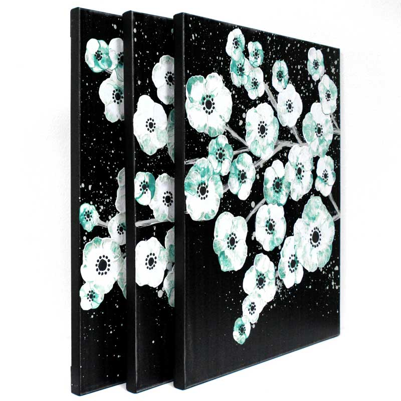 Side view of painting of teal and black cherry blossom on canvas triptych