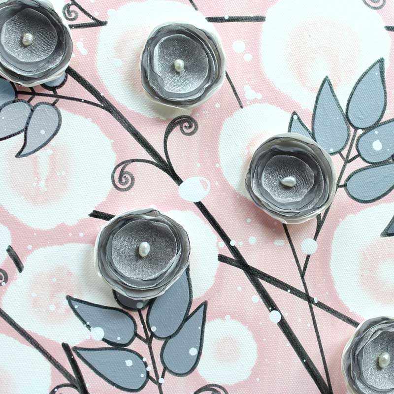 Close up of nursery wall art of pink and gray climbing flowers