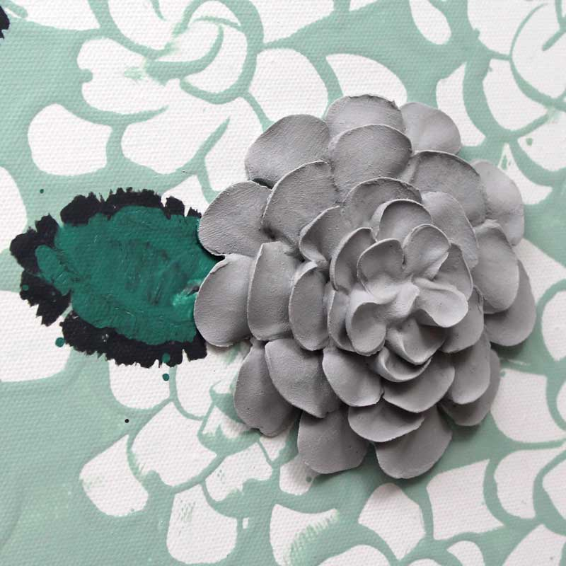 Close up of wall art of teal and gray dahlia flowers