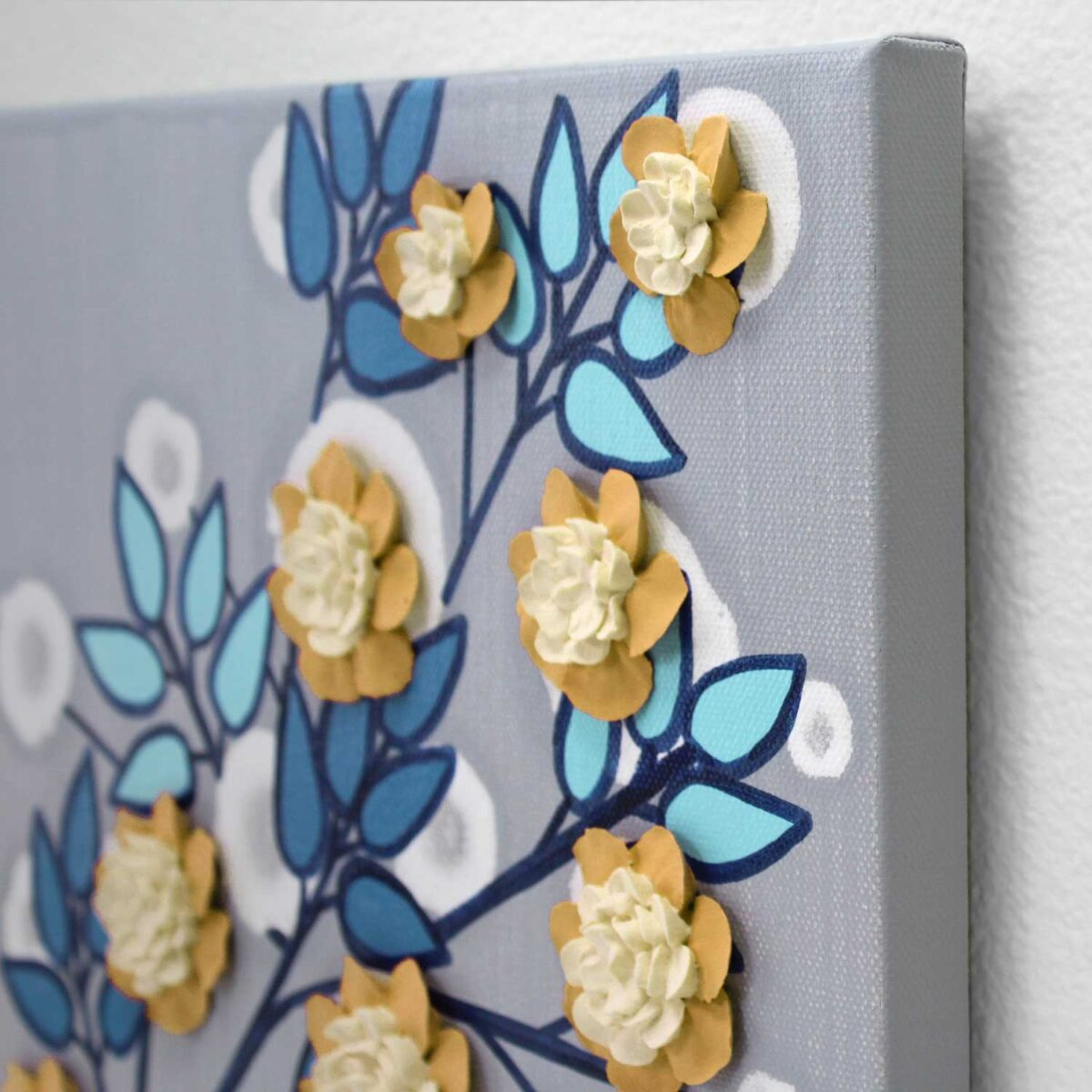 Angle view of wall art of flower branch in yellow, aqua, and indigo